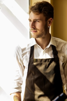 A man in an apron looks out the window