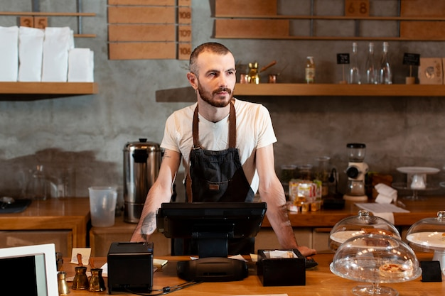 Man in apron posing at cash register