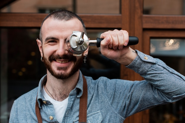 Man in apron posing with coffee machine component
