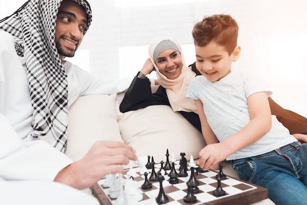 A man in arabic clothes plays chess with a little boy.