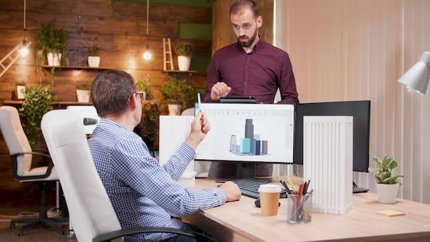彼のエンジニアの同僚に建物の建設構造を説明する男性建築家