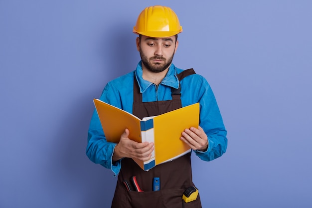 Man architect wearing helmet and brown apron, holding paper apron and reading information about new project, looks serious