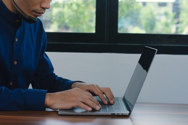 男性は自宅でコールセンターのヘッドフォンオンラインサポート、男性はコンピュータオンライン技術で働いています
