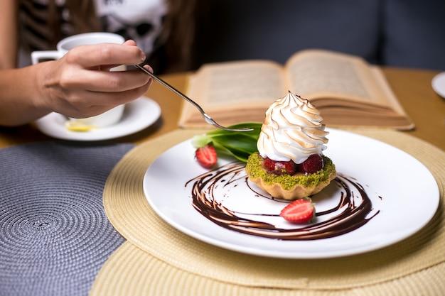 L'uomo sta andando a mangiare tartellette con vista laterale al cioccolato crema di fragole pistacchi