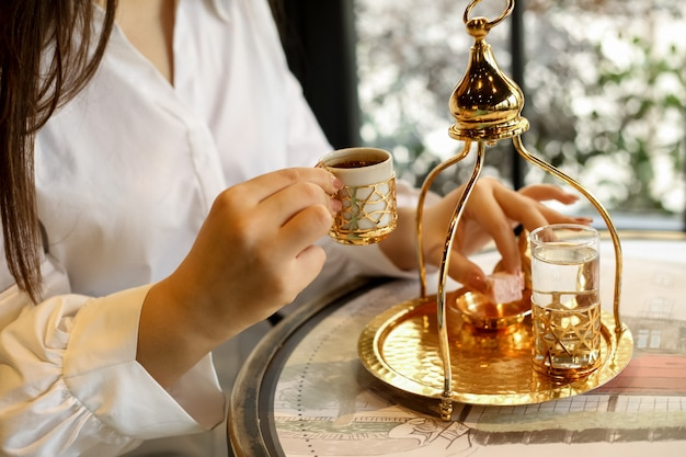男は伝統的な料理の水の砂糖の側面図でトルココーヒーを飲むつもりです。