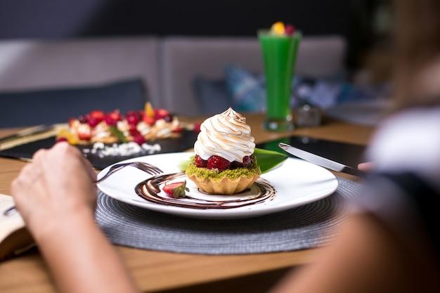 男はピスタチオのストロベリークリームチョコレートの側面図とタルトを食べるつもり