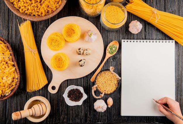 Man are going to write in notebook italian pastas spaghetti stelline linguini tagliolini mortar garlic top view copy space