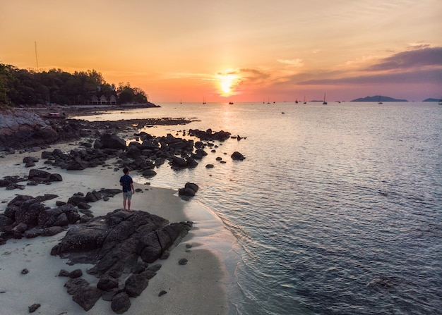 Man are sightseeing sunset on coastline in tropical sea