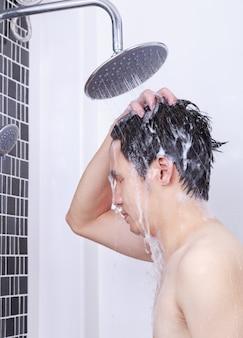 男はレインシャワーと髪を洗っている