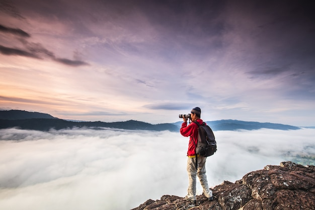 The man are taking photos  the sea of mist on high mountain.
