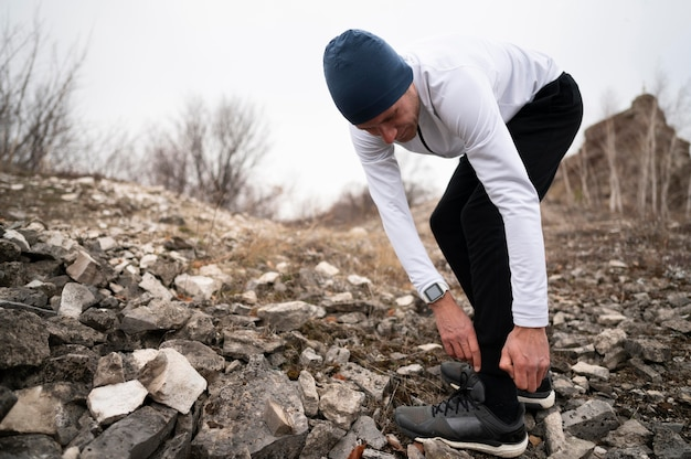 Man arranging his shoe in nature on trail
