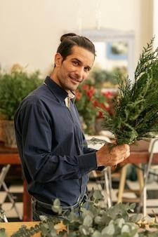 Человек расставляет растения и смотрит в камеру