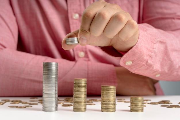 Мужчина расставляет стопки монет