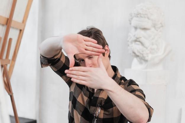 Художник человека делая рамку с его пальцами
