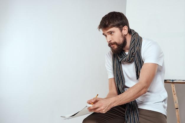 Художник мужчина рисует на мольберте кистью