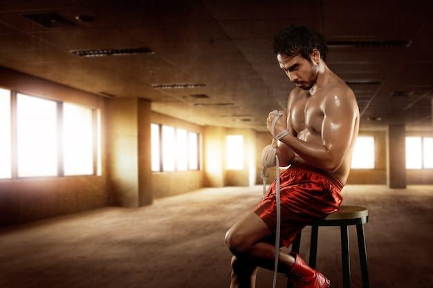 Man asian boxer sitting with wearing white strap
