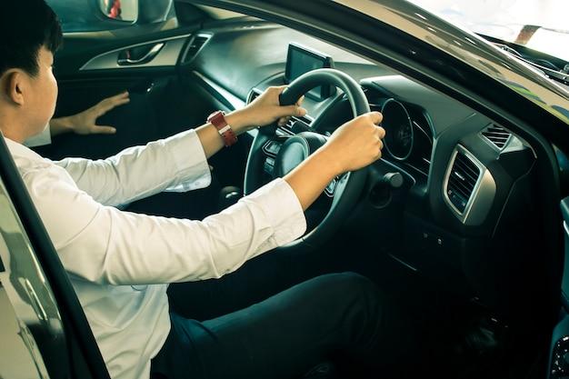 Мужчина азиатский вождение автомобиля на размытом фоне в выставочном зале