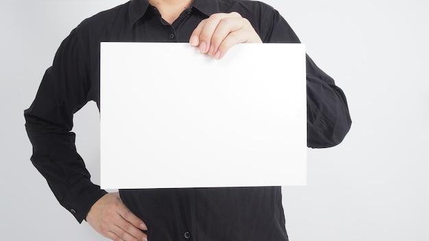 Доска чистого листа бумаги владением человека азиатская и носите черную рубашку на белой предпосылке.