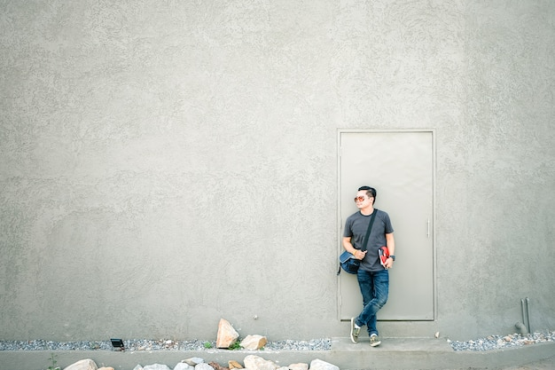 Man asian tourists standing in front of a gray wall.