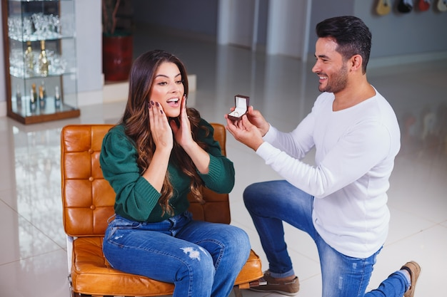 Man asking his girlfriend to marry him showing her the ring