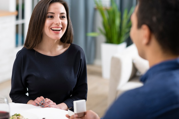 Мужчина просит свою улыбающуюся подругу выйти за него замуж