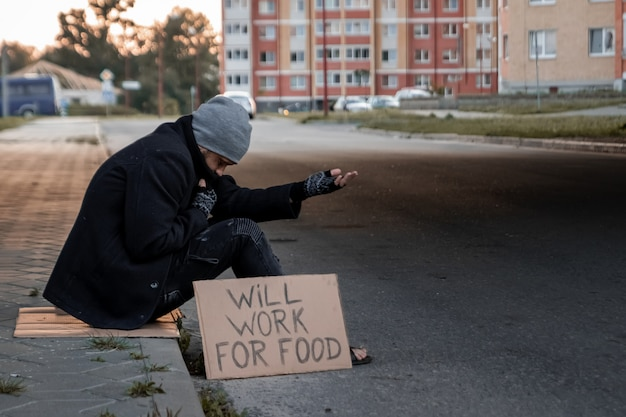 Man asks for alms on the street with a sign will work for food, homeless