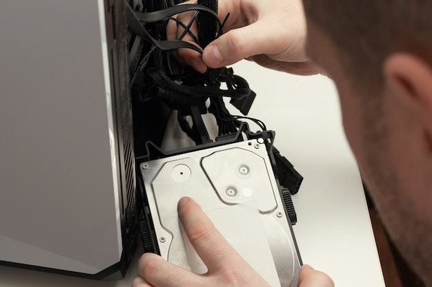 A man assembles a computer system connecting a hard drive close up