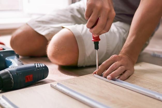 남자는 바닥에 앉아 집에서 손으로 가구를 조립