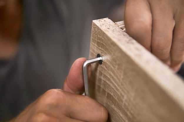 Man assembles furniture by hand at home, focus on fastener and hex key in his fingers