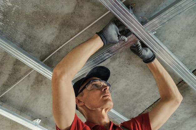 Мужчина собирает профильный металлический каркас для потолков из гипсокартона