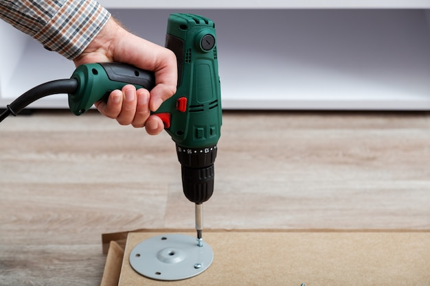 Man assembles table furniture with drill. assembly, furniture repair home master. male hand with drill on floor. copy space.