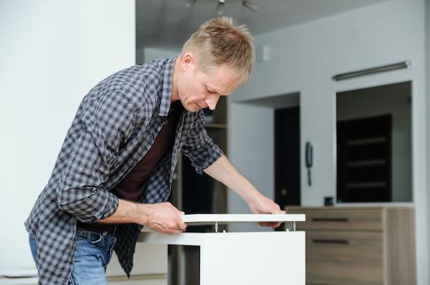 Мужчина собирает мебель в домашних условиях, устанавливает верх комода