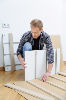 Man assembling furniture from chipboard boards