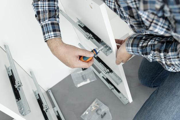 Мужчина собирает мебель с помощью отвертки