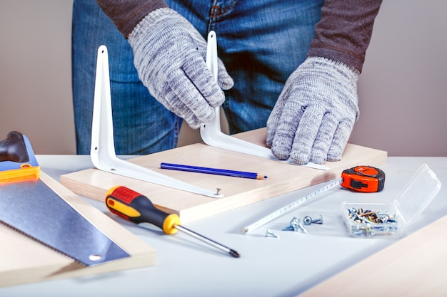 Man assembling furniture using manual tools. do-it-yourself project.