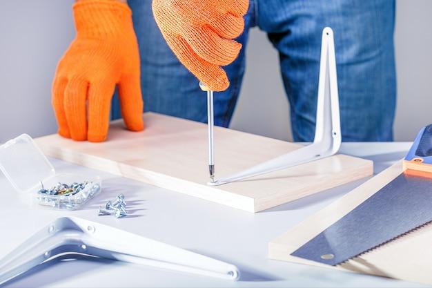 Man assembling furniture using screwdriver