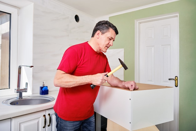 Man assembling kitchen cabinet with hammer and nails.