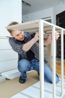 Мужчина собирает мебель дома, закрепляя каркас комода