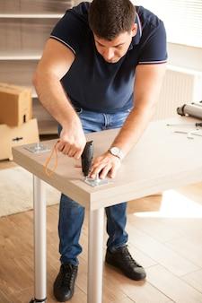 L'uomo monta i mobili per la nuova casa che hanno acquistato