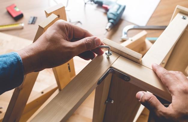 남자 조립 목재 가구, 드라이버 도구로 집 수리 또는 수리.