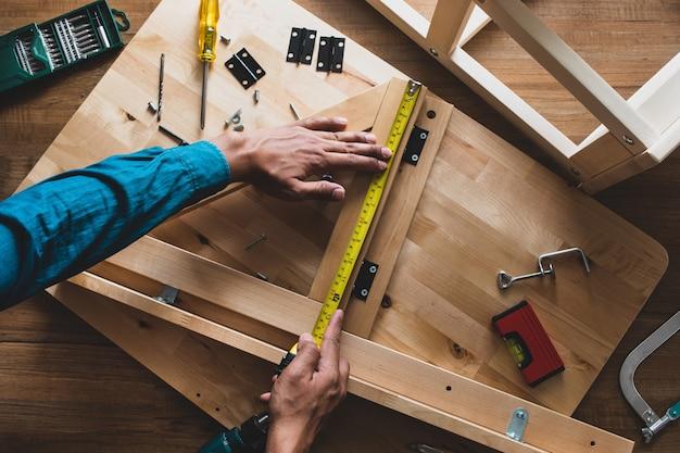 Мужчина собирает деревянную мебель, чинит или ремонтирует дом с рулеткой