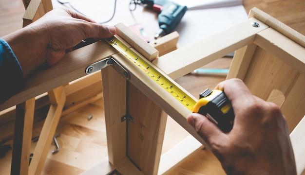 Человек собирает деревянную мебель, чинит или ремонтирует дом с желтой рулеткой.
