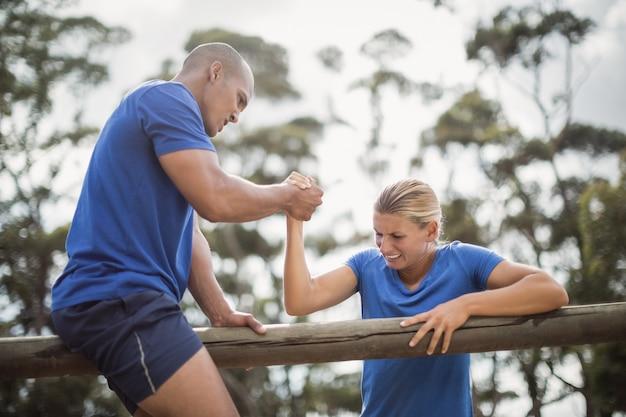 Мужчина помогает женщине преодолевать препятствия во время тренировки с препятствиями в учебном лагере