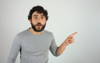 Man astonished showing direction and pointing with finger