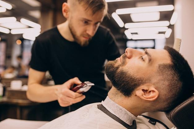 Мужчина в парикмахерской делает прическу и бороду