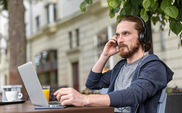 Человек на городской террасе работает на ноутбуке во время ношения наушников