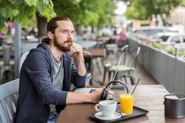Человек на городской террасе работает с ноутбуком