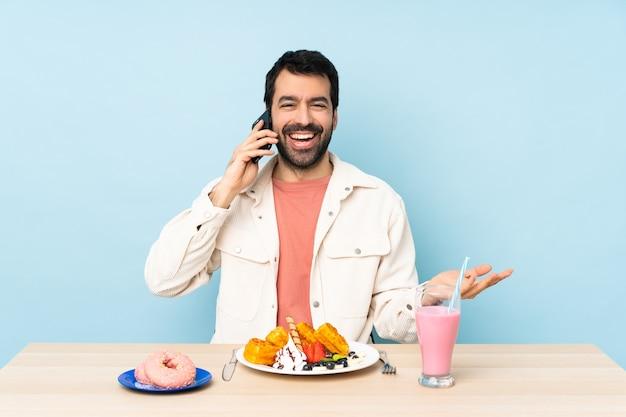 아침 식사 와플과 밀크 쉐이크가있는 테이블에있는 남자가 누군가와 휴대 전화로 대화를 나누고 있습니다.