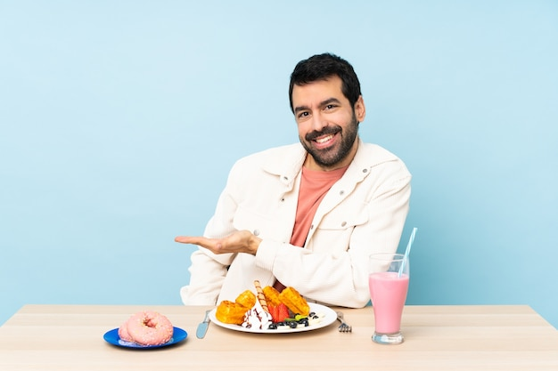 朝食のワッフルとミルクセーキを持っているテーブルの男は、に向かって笑顔を見ながらアイデアを提示します