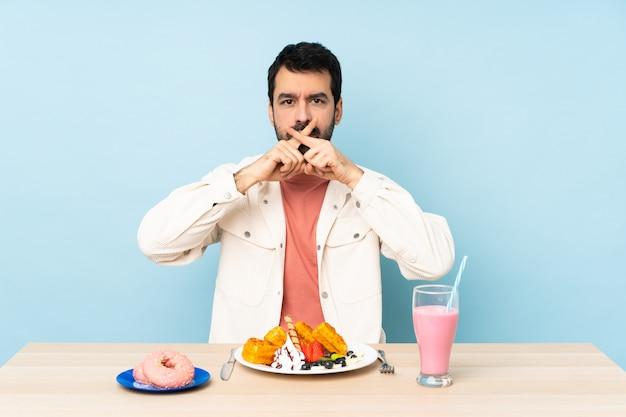 아침 식사 와플과 침묵 제스처의 표시를 보여주는 밀크 쉐이크 테이블에 남자